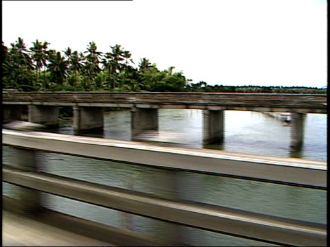 vidéos et rushes de august 4 1985 ds view from a vehicle as it drives over a bridge and down a shanty town street / philippines - cahute