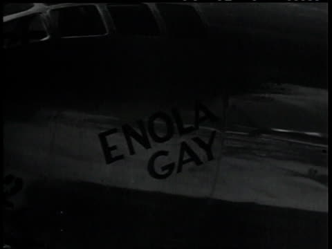 august 6, 1945 montage crew of enola gay stands in front of plane that dropped nuclear weapon on japan / guam - 大量破壊兵器点の映像素材/bロール