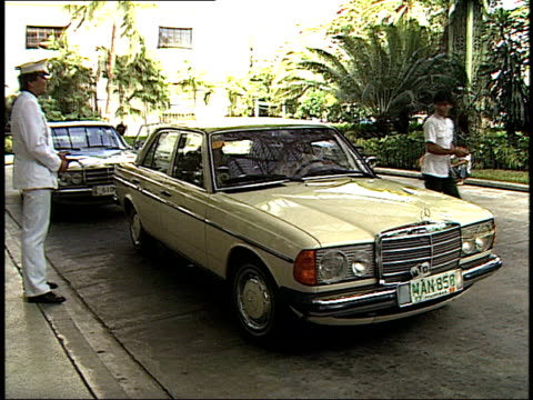 August 6 1985 PAN Hotel employees assisting guests into and out of their Mercedes cars / Manila the Philippines