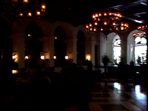 august 6, 1985 hotel guests sitting in and walking through the lobby beneath an elegant chandelier / manila, the philippines - lobby stock videos & royalty-free footage