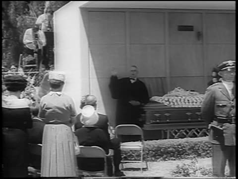 B/W August 8 1962 clergyman by coffin performing funeral ceremony outdoors for Marilyn Monroe / newsreel