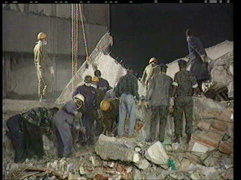 stockvideo's en b-roll-footage met august 8 1998 film montage people and crane in front of aftermath of car bombing at us embassy/ ms rubble and sign/ ms workers digging/ ws wreckage/... - 1998