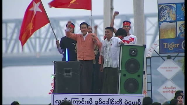 aung san suu kyi campaigns ahead of byelection supporters of national league for democracy stand on stage at rally with loudspeakers playing music... - music stand stock videos and b-roll footage