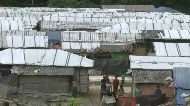 stockvideo's en b-roll-footage met aung san suu kyi denies rohingya genocide at the hague t131118032 / tx ext high angle of refugee village man and three children standing behind fence - crime and murder