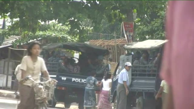 Aung San Suu Kyi stands trial for breaching house arrest terms Police trucks carrying armed police along near prison perimeter