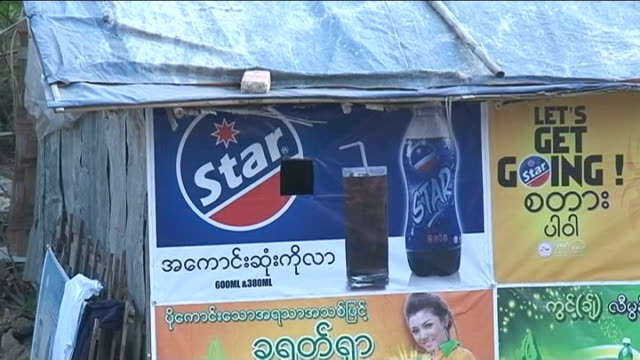 aung san suu kyi's party wins 44 seats in parliamentary by-elections; hole in 'star' cola poster people clapping sot man saying 'welcome to burma... - poster stock videos & royalty-free footage