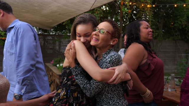 vídeos de stock e filmes b-roll de ms aunt embracing niece after outdoor family dinner party - abraçar