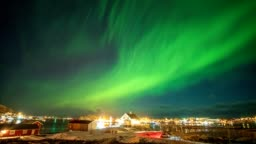 Aurora Borealis (Northern lights) above fishing village in arctic ocean