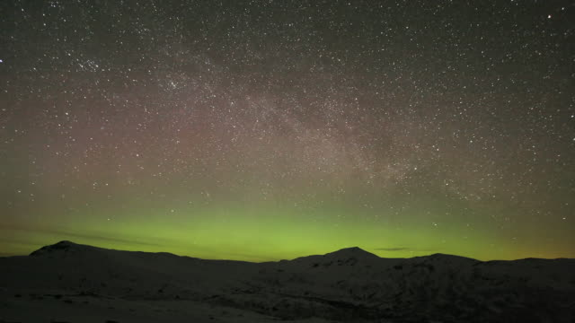 Aurora borealis and rotating stars over snowy mountains timelapse