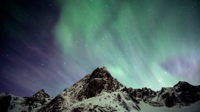 aurora borealis moving on snowy mountain at lofoten islands - esposizione lunga video stock e b–roll