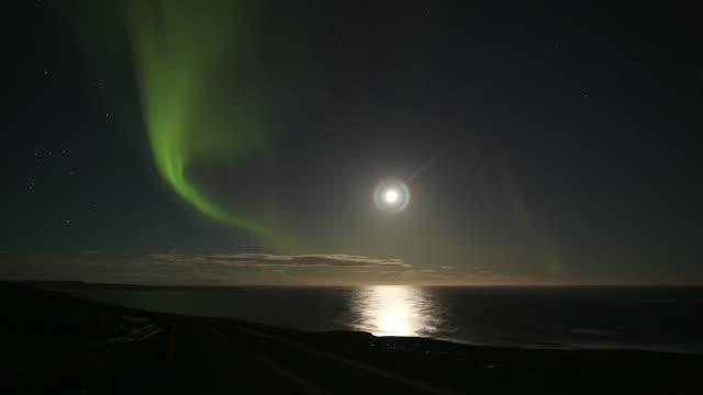 Aurora Borealis over ocean bay with moon.