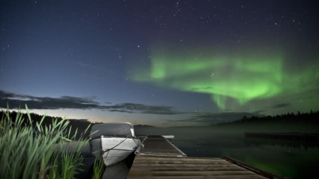T/L WS Aurora borealis over Vee Lake, pier and boat in foreground / Yellowknife, Northwest Territories, Canada