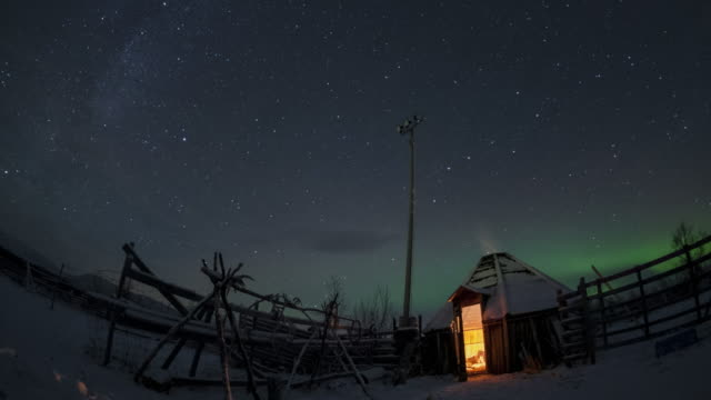 Aurora dancing above a traditional hut in northern Lapland in Sweden