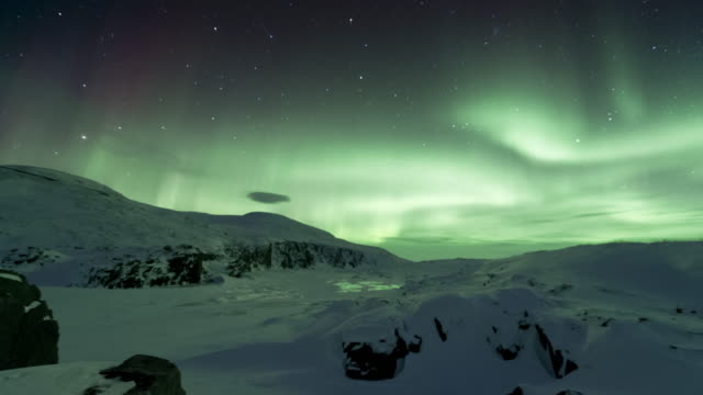 T/L of aurora on frozen ridge in Arctic