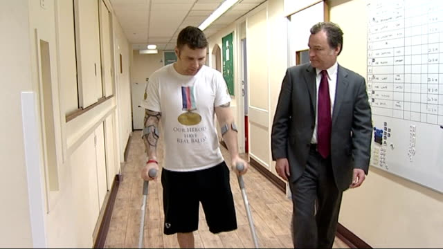 Austen along corridor on crutches after amputation talking to reporter Corporal Ross Austen interview about how he has no regrets about amputation SOT