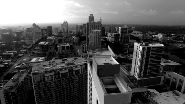 austin texas black and white epic sunrise aerial vast texas hill country town flying close to highrise and skyscrapers right above condo - viraggio monocromo video stock e b–roll