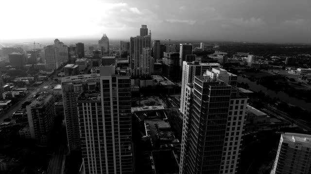 austin texas black and white epic sunrise aerial vast texas hill country town flying close to highrise and skyscrapers - viraggio monocromo video stock e b–roll
