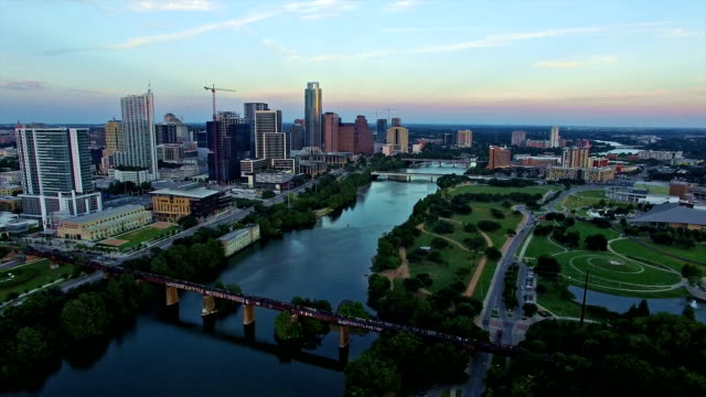 vídeos de stock e filmes b-roll de austin texas downtown over town lake at colorful sunset summer central texas passing over bridges - town