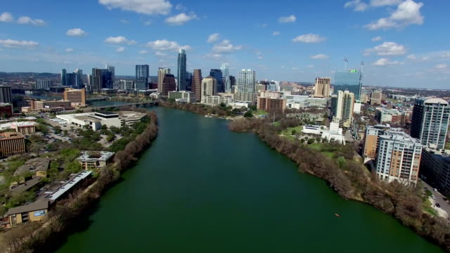 vídeos de stock e filmes b-roll de austin texas on sunny partly cloudy day passing clouds and bright day over town lake backing up really far - town