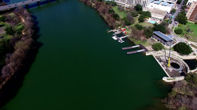 vídeos de stock e filmes b-roll de austin texas on sunny partly cloudy day passing clouds and bright day over town lake down to up camera pan to austin skyline - town