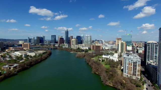 vídeos de stock e filmes b-roll de austin texas on sunny partly cloudy day passing clouds and bright day over town lake blue paradise sky low backing up - town