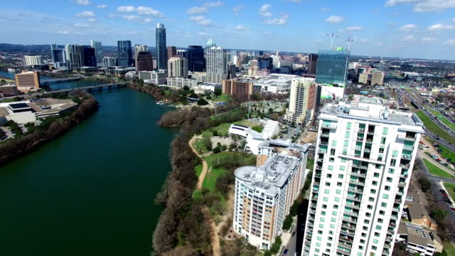 vídeos de stock e filmes b-roll de austin texas on sunny partly cloudy day passing clouds and bright day over town lake side pan by high condo - town