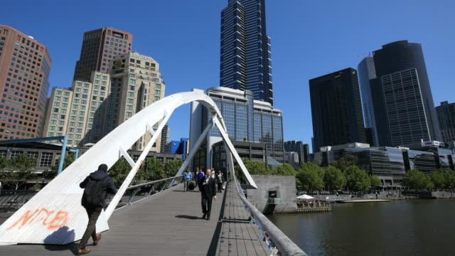 Australia Melbourne foot bridge Yarra River includes people with suitcases