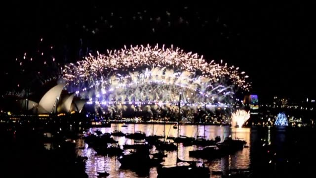 australia rings in the new year with bumper crowds gathering to watch a firework extravaganza on sydney's glittering harbor - bumper stock videos & royalty-free footage