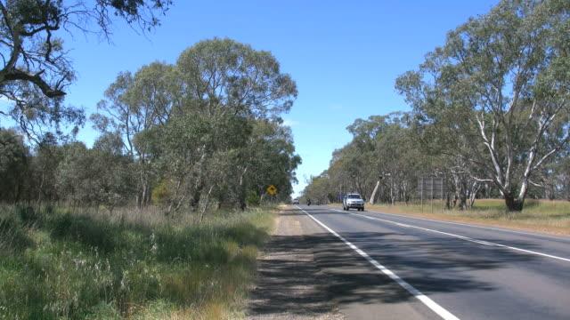 australia road with traffic and kangaroo sign - straßenrand stock-videos und b-roll-filmmaterial