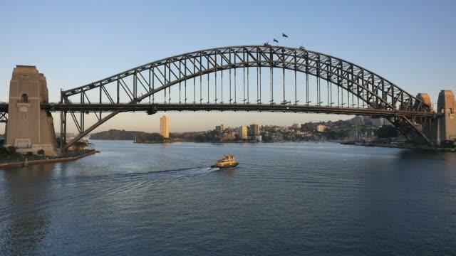 australia sydney boat continues under harbor bridge - ferry stock videos & royalty-free footage