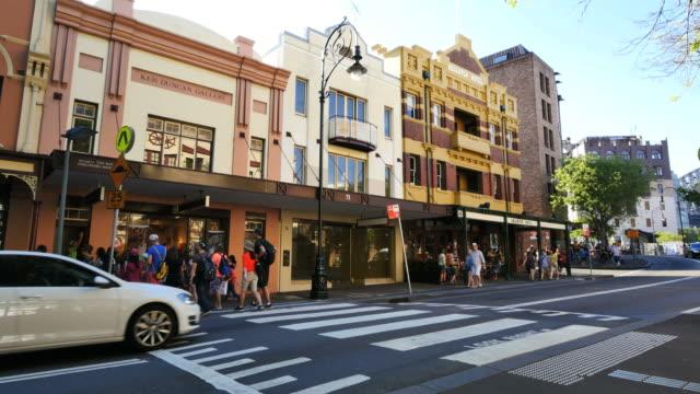 Australia Sydney people crossing street by historic buildings