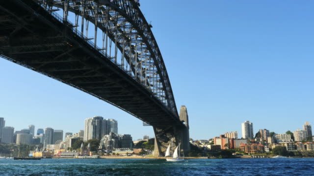australia sydney sailboat moves under harbour bridge - international landmark stock videos & royalty-free footage