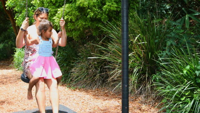 australian aboriginal woman and girl playing on a swing - swinging stock videos & royalty-free footage