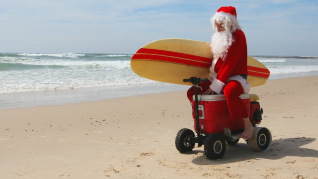 vídeos de stock e filmes b-roll de australian christmas santa claus pretending to ride a motorised esky cooler on the beach - balde de gelo