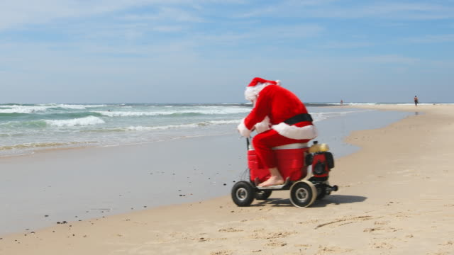 australian christmas santa claus riding a motorised esky cooler on the beach - cooler container stock videos and b-roll footage