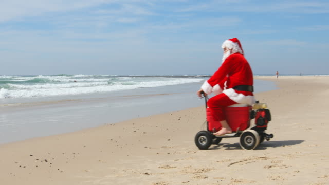 vídeos de stock e filmes b-roll de australian christmas santa claus riding a motorised esky cooler on the beach - balde de gelo