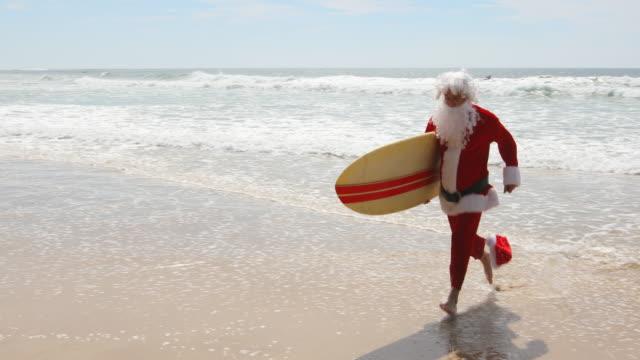 stockvideo's en b-roll-footage met australische kerst surfen kerstman draait op het strand met een surfplank - surfbord