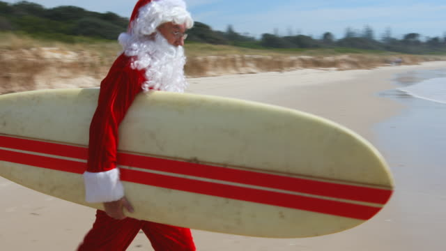 vídeos de stock e filmes b-roll de australian christmas surfing santa claus running on the beach with a surfboard - pai natal