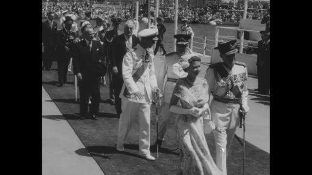 vídeos y material grabado en eventos de stock de australian flag flutters on pole, with sydney harbor behind / montage queen elizabeth ii and philip, duke of edinburgh, walk with australian... - visita de estado