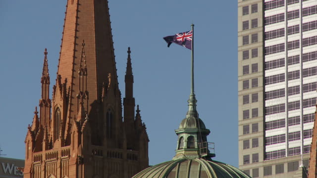 MS Australian flag on top of Flinders Street Station with St Paul's Cathedral tower in background/ Melbourne, Australia