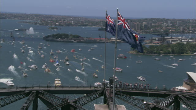 australian flags fly above sydney harbor where ferry boats race. - oceania stock videos & royalty-free footage