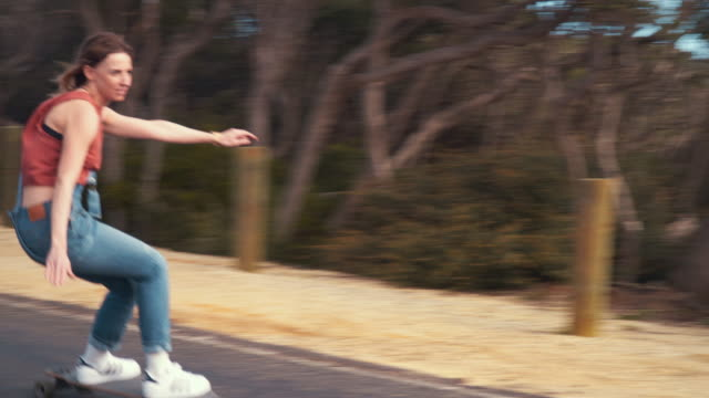 australian locals in sport: female longboard skater riding in an empty road - dungarees stock videos and b-roll footage