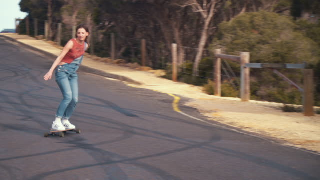Australian Locals in Sport: female longboard skater riding in an empty road