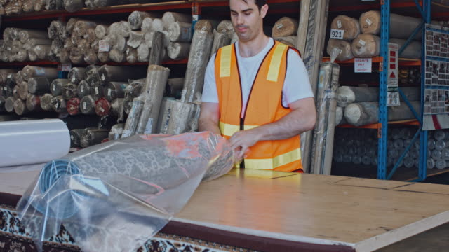 Australische männlichen Arbeitnehmer Vorbereitung Teppiche bereit, im Lager zu liefern