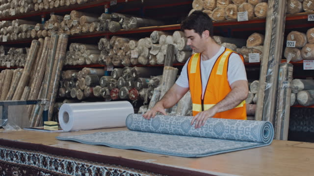 Australian male worker rolling carpet at warehouse