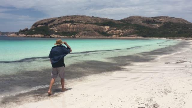 australian man walking along lucky bay in western australia - western australia bildbanksvideor och videomaterial från bakom kulisserna