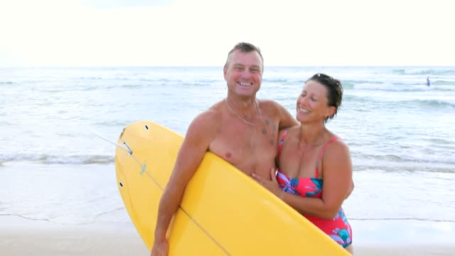 australian mature age surfing couple - quarantenne video stock e b–roll