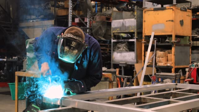 australian metal worker welding in factory - gente comune video stock e b–roll
