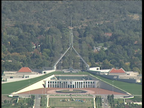 australian parliament building traffic on roads trees in background canberra - parliament building stock videos & royalty-free footage