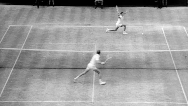 Australian Roy Emerson beats his fellow countrymen Fred Stolle in men's tennis singles at Wimbledon / spectators clapping / Emerson jumps over net...